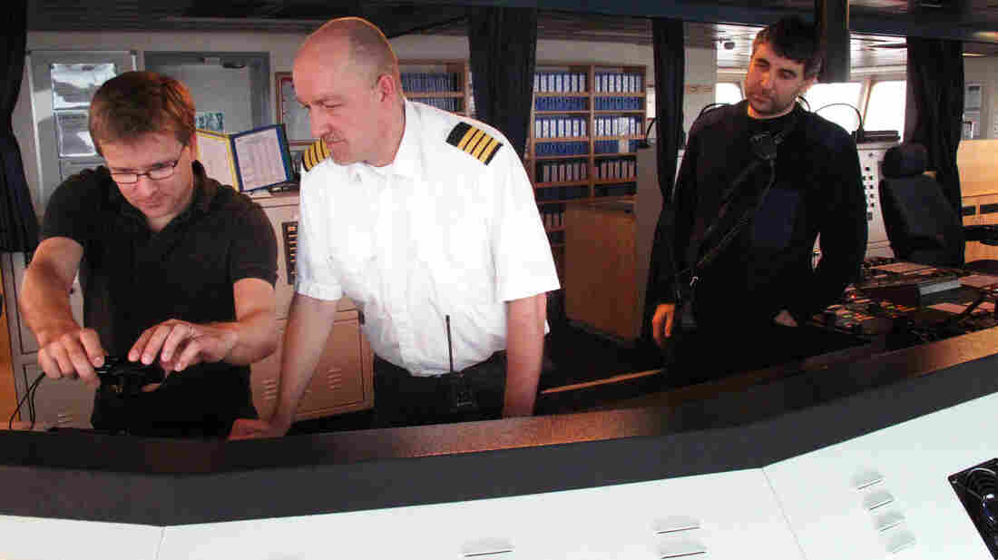 Captain Jes Meinertz (center) and pilot Pawel Pidzikiewicz (right) take the ship out of the port of Gdansk into the Baltic Sea.