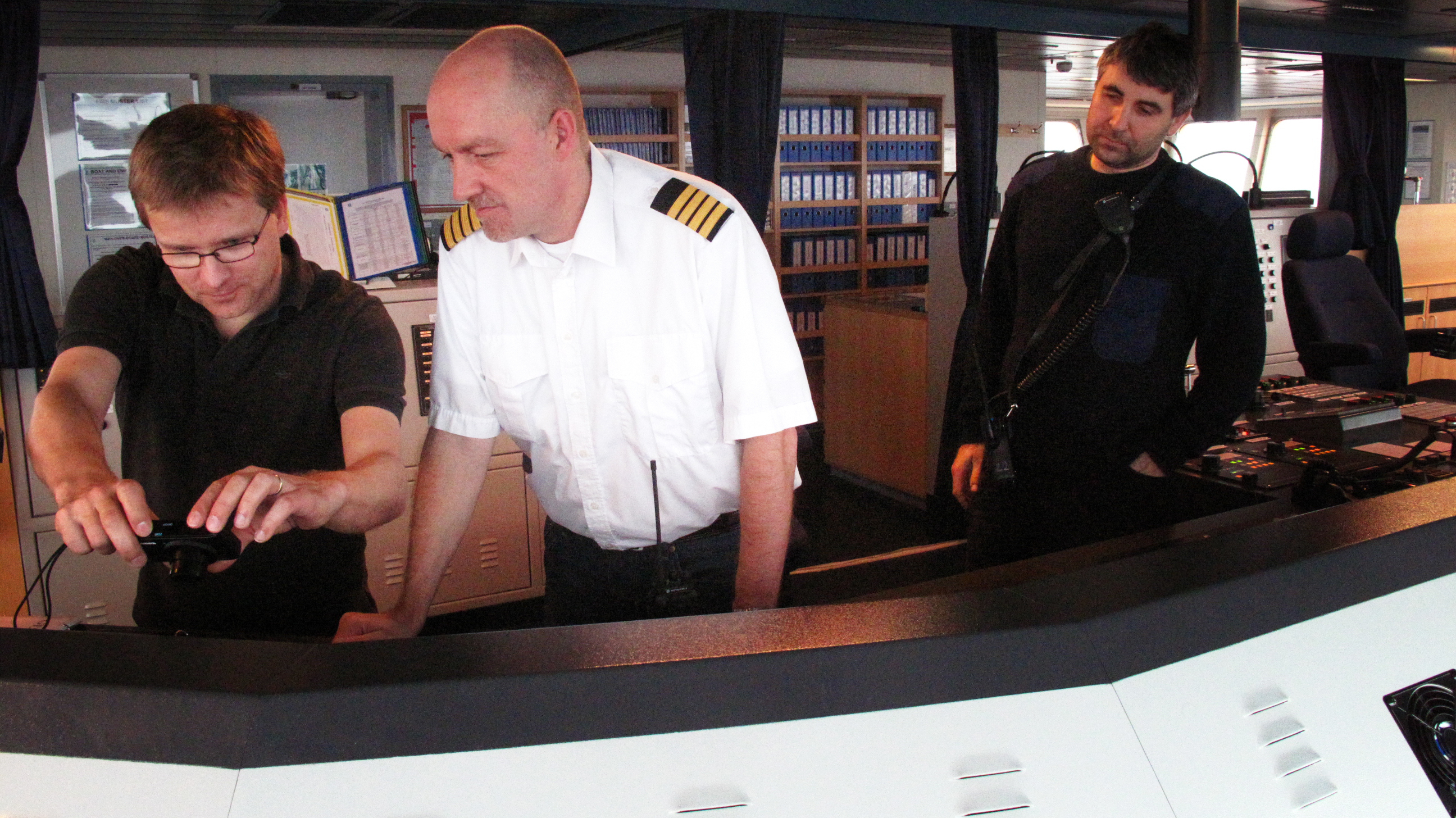 Captain Jes Meinertz (center) and Pawel Pidzikiewicz, (right) the ship's Polish pilot, take the ship out of port of Gdansk into the Baltic Sea.