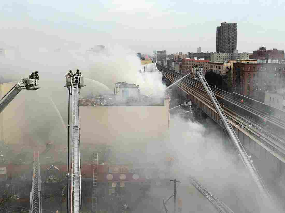 Firefighters try to put out a fire after a reported explosion and building collapse