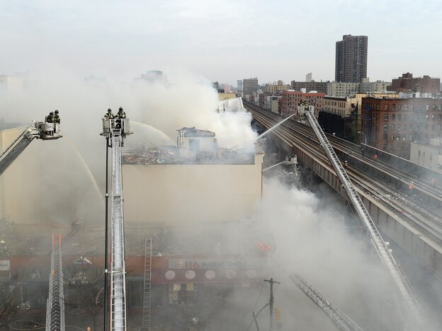 Firefighters try to put out a fire after a reported explosion and building collapse in the Harlem neighborhood of New York City on Wednesday.