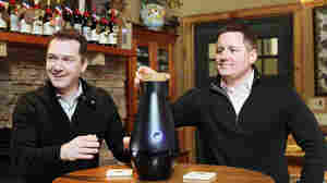 Philip James, Chairman of CustomVine, and Kevin Boyer, President and CEO of CustomVine, film a video to promote The Miracle Machine, which turns water into wine with the use of an app.