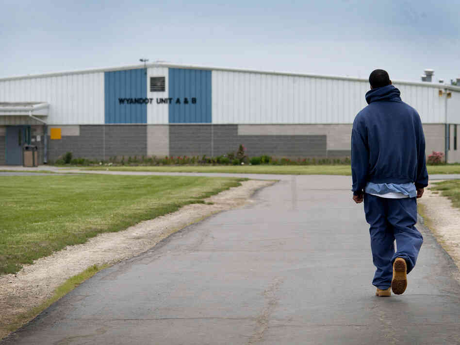 An inmate walks through the yard at the North Central Correctional Institution in Marion, Ohio, which recently switched to private management.