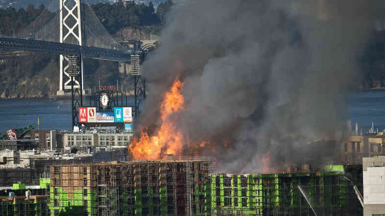Flames leap from the roof of the under-construction apartment building that caught fire Tuesday in San Francisco.