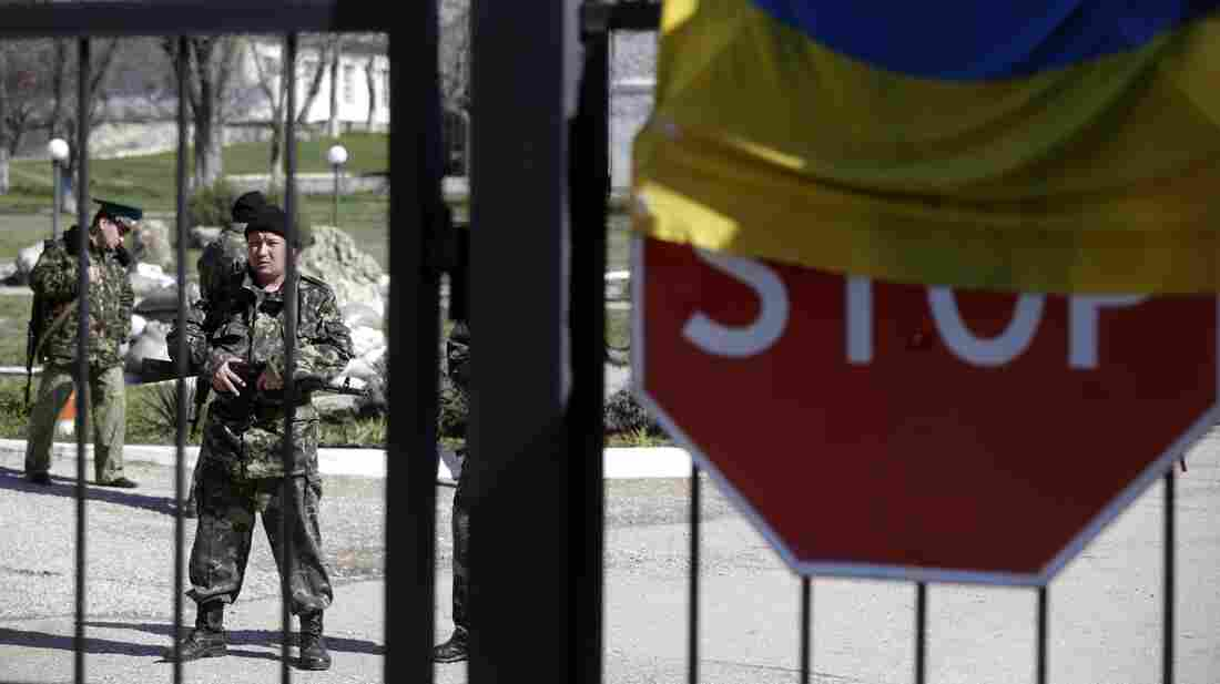 Their nation's flag was draped over a stop sign last week as Ukrainian soldiers stood guard inside part of the Belbek air base outside Sevastopol, Crimea. Other soldiers, said to be Russian troops, took over most of the base.