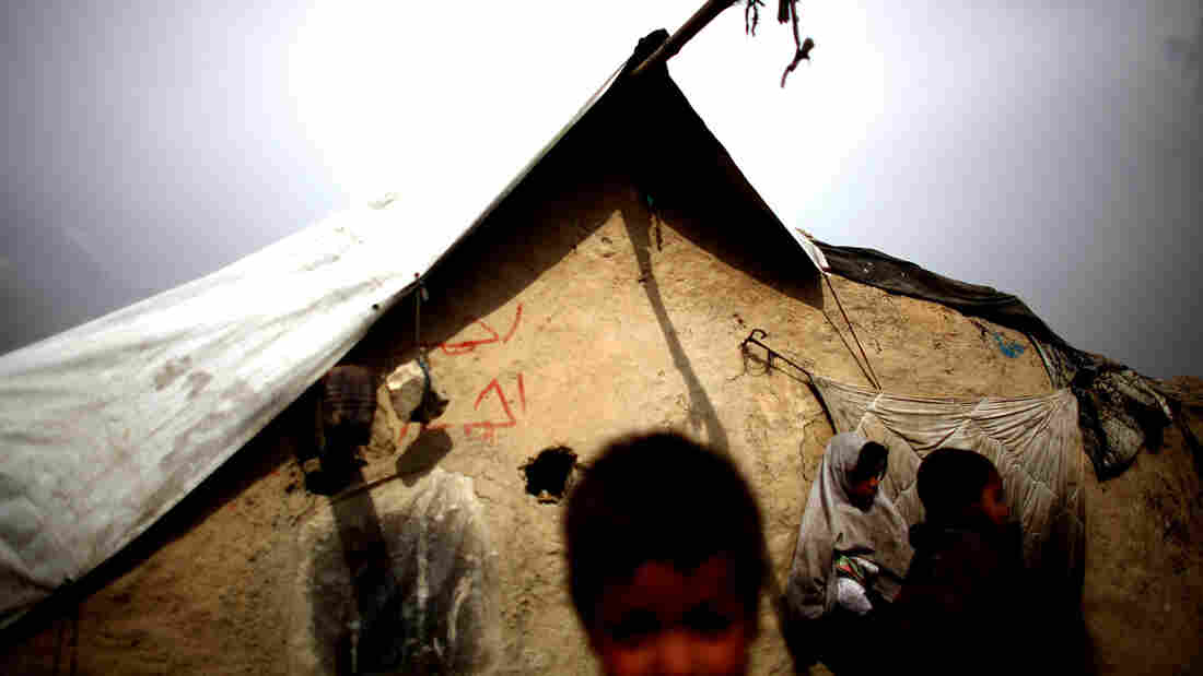 Children gather outside of their mud walled home in the Nasaji Bagrami camp for internally displaced Afghans in Kabul.