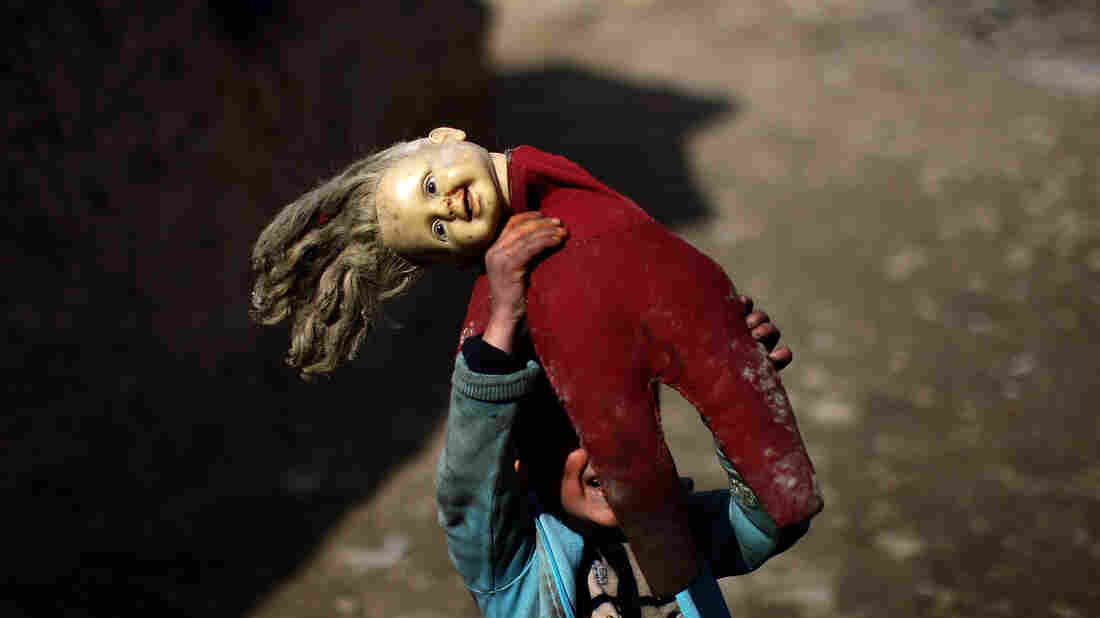 A child plays with a ragged doll at the Nasaji Bagrami camp for internally displaced Afghans in Kabul.