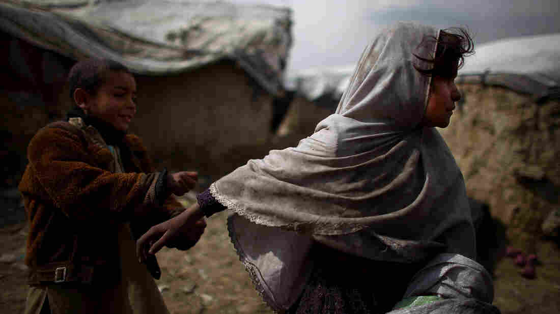 A little girl runs away from her brother while playing outside of the family's home in the Nasaji Bagrami camp for internally displaced Afghans in Kabul.