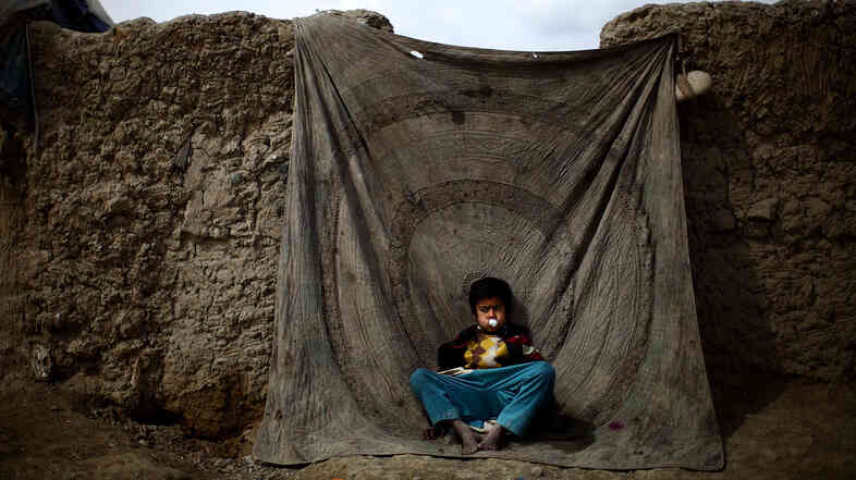 A boy sits blowing bubbles against a blanket used as a door to a home in the Nasaji Bagrami camp for internally displaced Afghans in Kabul.