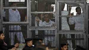 Australian journalist Peter Greste (center) of Al Jazeera and his colleagues stand inside the defendants' cage during their trial for allegedly supporting the Muslim Brotherhood at Cairo's Tora prison on Mar. 5.