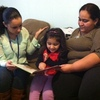 Stephanie Taveras (left) visits Julia Alfaro and her 3-year-old daughter, Ayleen, to read and discuss her vocabulary progress.