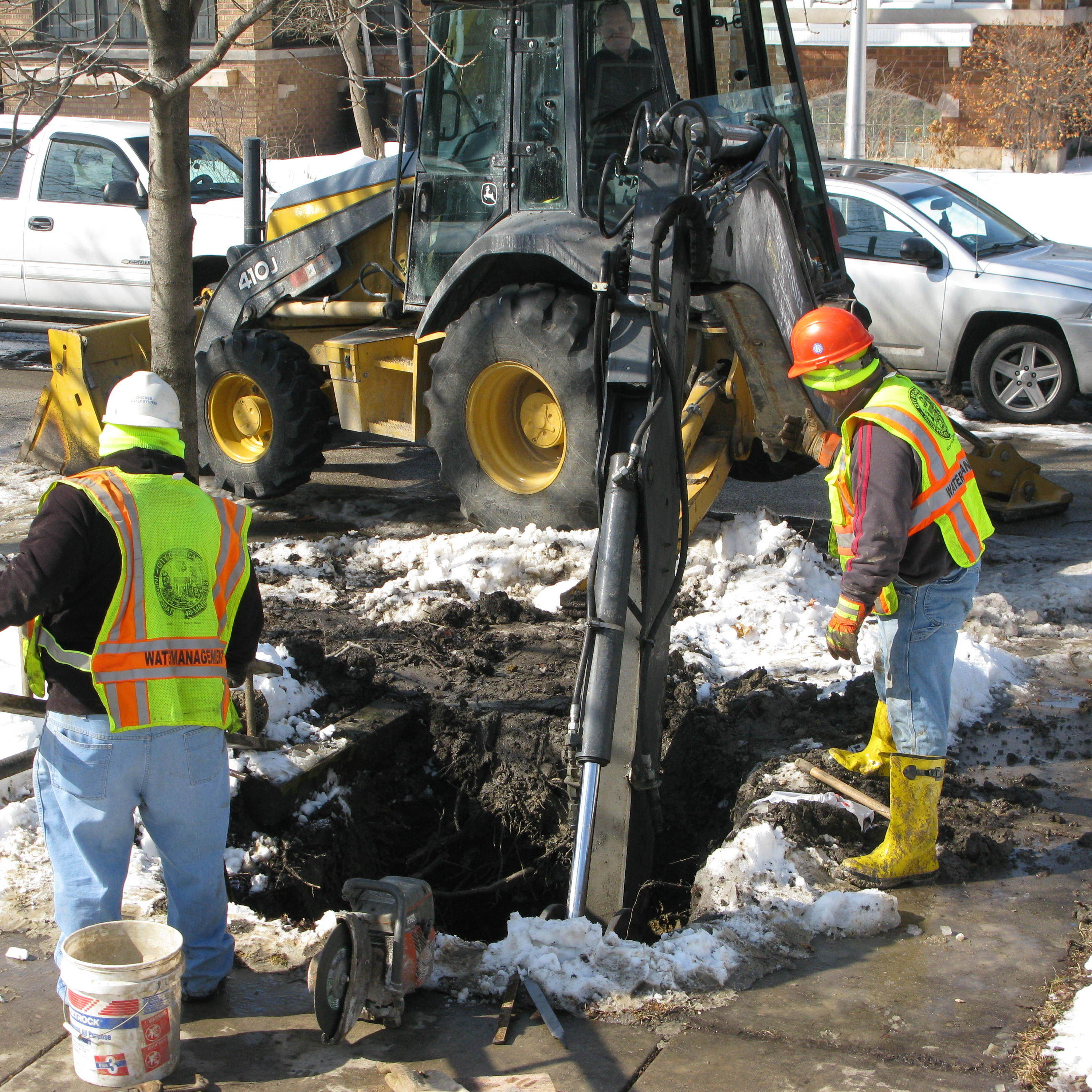 A backhoe operated by a Chicago Department of Water Management worker digs a trench about 5 feet deep so other workers can repair a leak in a waterline deep underground.