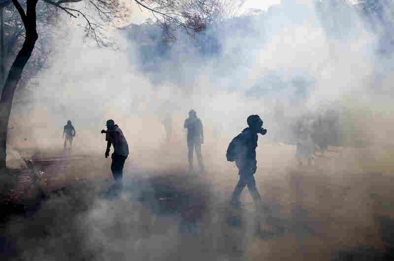 Demonstrators walk through a cloud of tear gas fired by the police.
