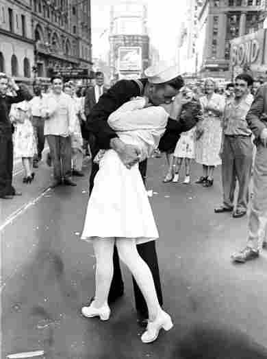As pedestrians watch, an American sailor passionately kisses a white-uniformed nurse in Times Square to celebrate the long awaited-victory over Japan on August 14, 1945.