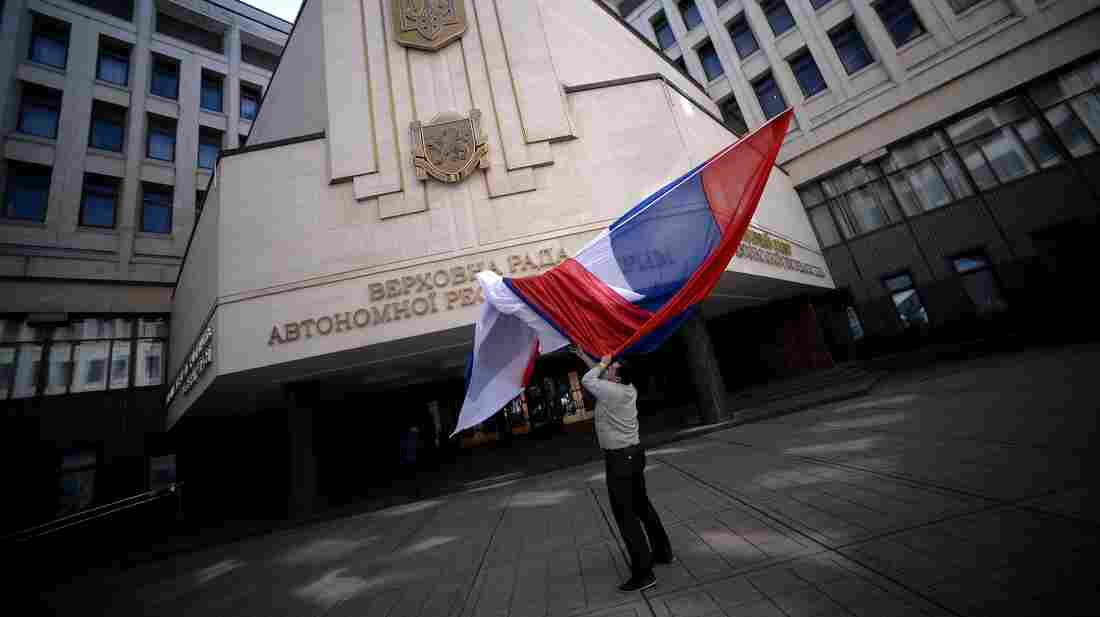 A Russian flag blows outside the entrance of Crimea's parliament building in Simferopol on Thursday. Crimeans vote Sunday on whether they want to join Russia, though the international community says it will not recognize the ballot.