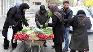 Iranian shoppers buy vegetables from a street vendor in Tehran last November, a day after a six-month nuclear deal took effect. The U.S. says crippling sanctions — which caused prices for necessities like bread, rice and soap to increase — forced Iran's hand.
