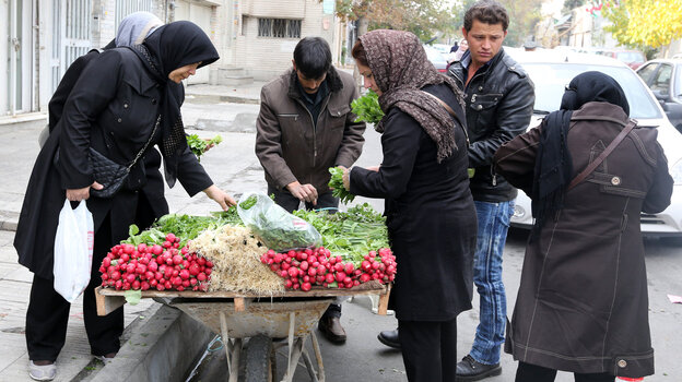 Iranian shoppers buy vegetables from a street vendor in Tehran last November, a day a