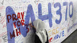 At Kuala Lumpur International Airport on Friday, a woman writes on a banner full of messages about the 239 missing passengers and crew of Malaysia