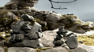 A pair of rocks sitting on a hillside.