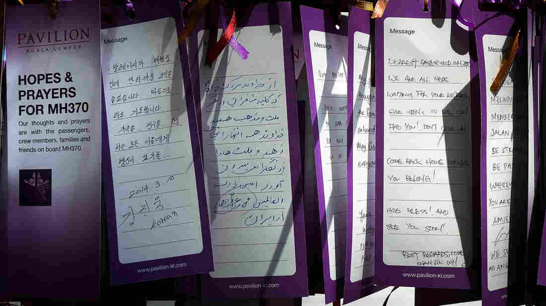 Multi-lingual cards about missing Malaysia Airlines Flight 370 line a wall at a mall in