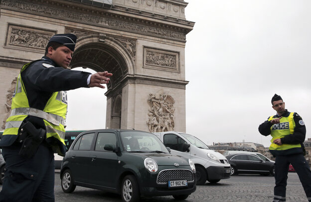 Police were checking cars throughout Paris on Monday, including near the Arc de Triomphe, as the city tried to cut air pollution by instituting odd-even driving restrictions.