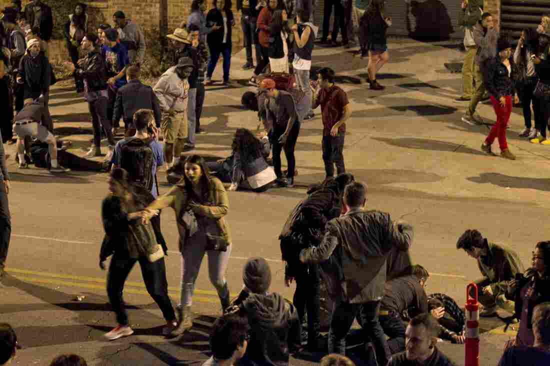 Bystanders rush to help those who were struck by a vehicle early Thursday on Red River Street in Austin, which was crowded with people headed to South by Southwest events.