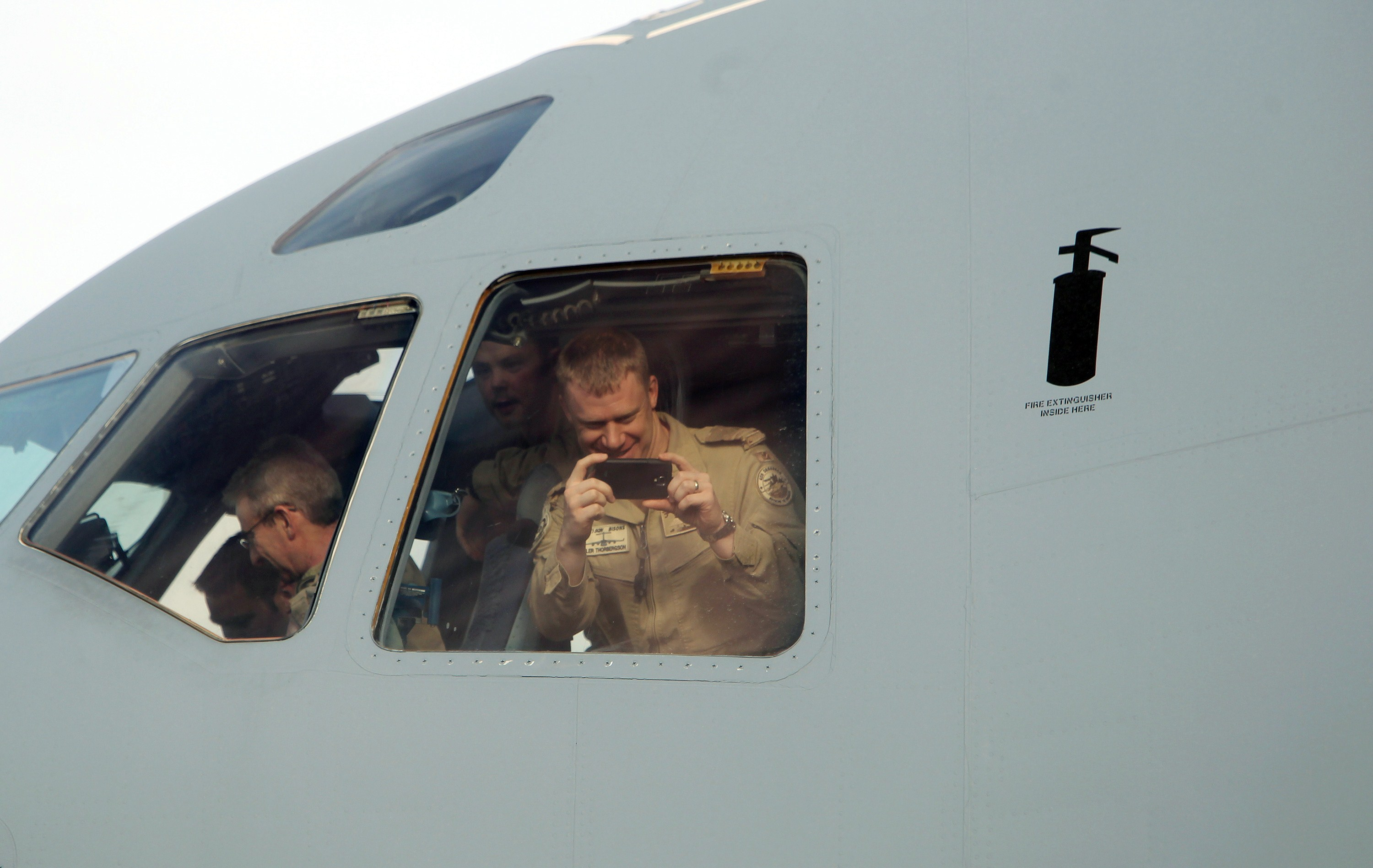 Soldiers take photos from the cockpit of the plane carrying the last of Canada's troops in Afghanistan.