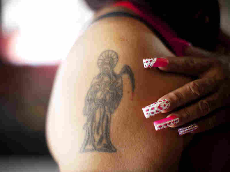 Claudia Rosales has several tattoos of Santa Muerte on her arms, chest and back.