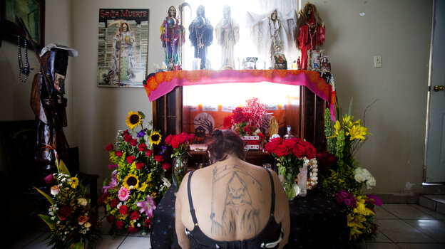 Claudia Rosales kneels in front of her home altar devoted to Santa Muerte, or Saint Death. Rosales put up a statue of the saint in the city that was taken down by the mayor of Matamoros.