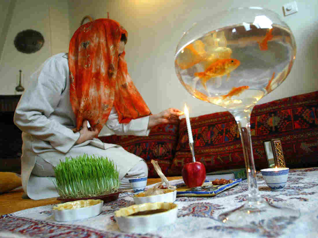 An Iranian woman in Tehran lights a candle on the ceremonial Nowruz table on the first day of the Iranian new year, March 2004. Some families add goldfish to the table to represent life.