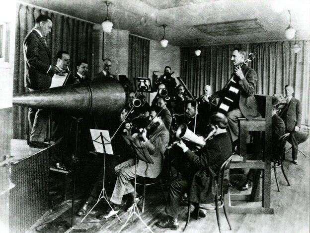 Before 1925, musicians like the Victor Orchestra, conducted by Rosario Bourdon, performed in front of a flared metal horn. An attached stylus would vibrate with the energy of the sound waves and etch them onto a wax rotating cylinder or disc — recording formats that are now very fragile.