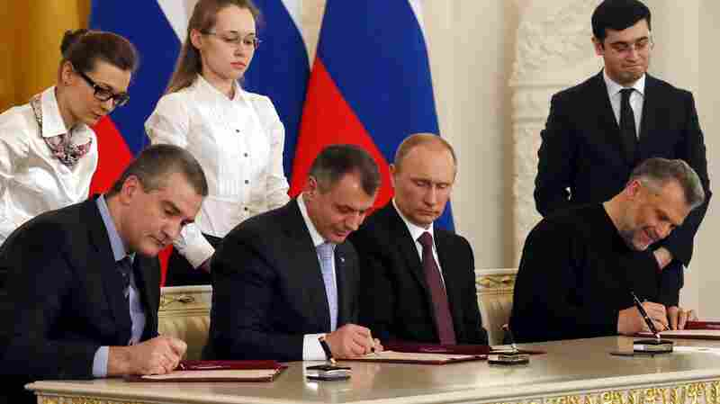 Russian President Vladimir Putin looks on as Crimean leaders sign a treaty for Crimea to join Russia on Tuesday. In response, Western countries have imposed limited sanctions.