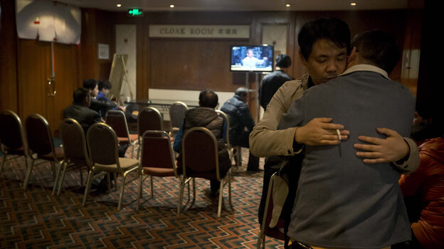 Relatives of Chinese passengers aboard the missing Malaysia Airlines flight comfort each other as they wait for