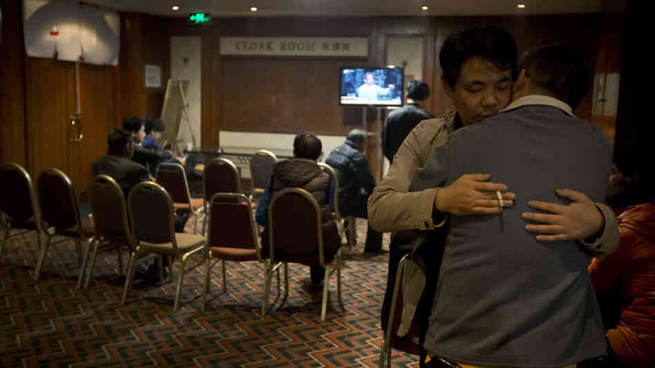 Relatives of Chinese passengers aboard the missing Malaysia Airlines flight comfort each other as they wait for a news briefing by airli