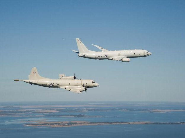 A P-8A Poseidon (top) and a P-3 Orion are shown flying off the coast of Maryland.