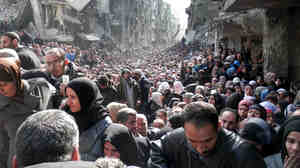This photo taken earlier this year shows residents of Yarmouk, a neigh