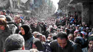 This photo taken earlier this year shows residents of Yarmouk, a neighborhood of Palestinians in Syria, lining up as far as the eye can see to receive food supplies.
