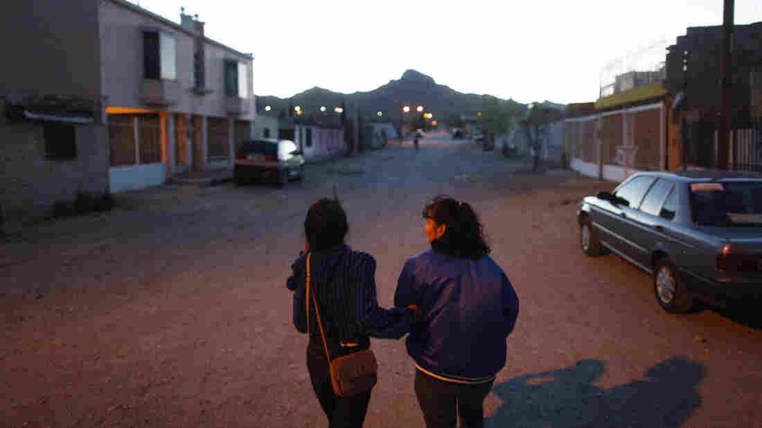 Yvonne Navarro walks through her Juarez neighborhood with her daughter, also named Yvonne, who at 16 is the same age her mother was when her mother went to work in maquiladoras.