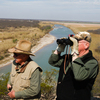 Dob Cunningham (left) and his friend Larry Johnson look over the edge of Cunningham's 800-acre ranch in Quemado, Texas.