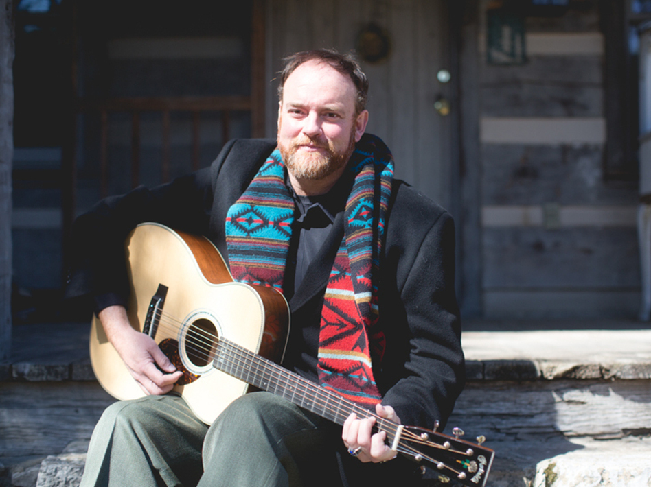 John Carter Cash relaxes on the cabin's front steps.