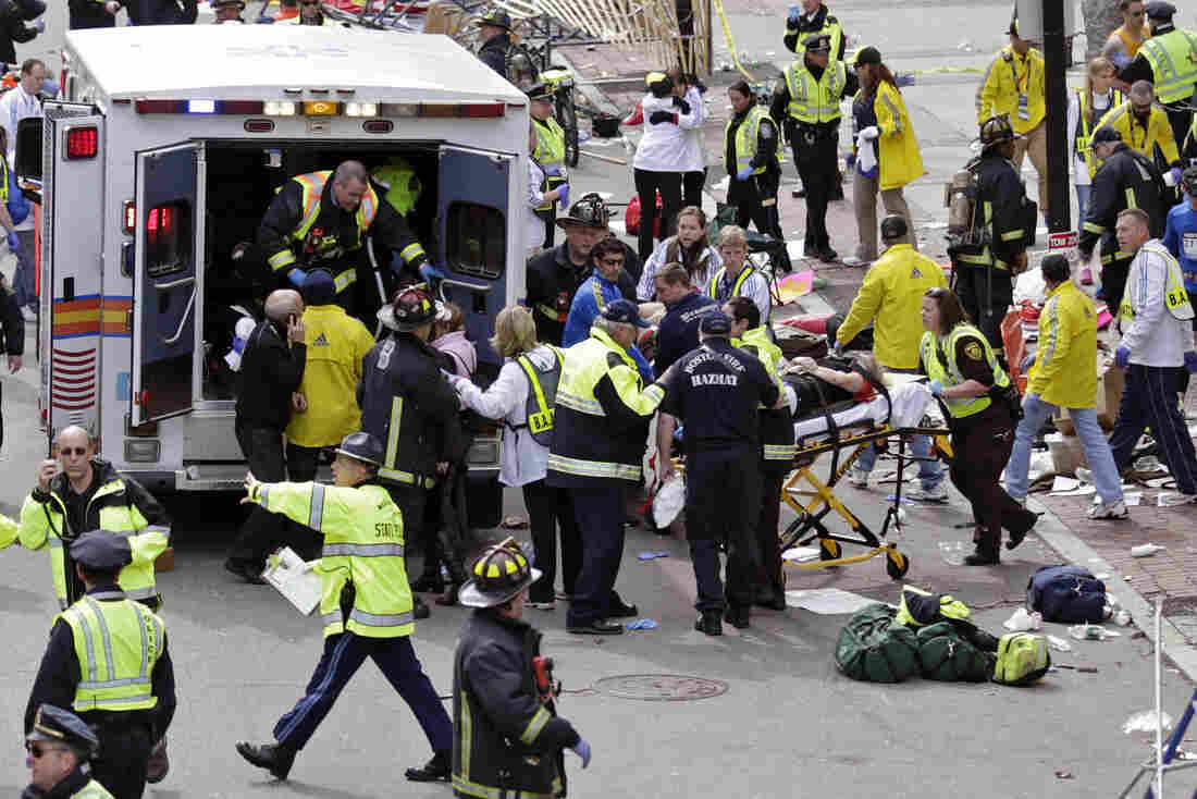 Amelia Nelson, next to the ambulance in the blue and white jacket, aids injured people at the finish line of the 2013 Boston Marathon on April 15, 2013.