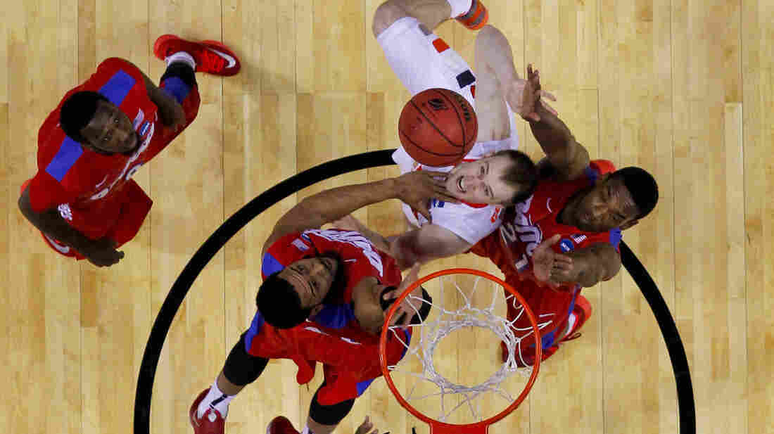 Syracuse's Trevor Cooney (No. 10) shoots between Dayton's Devon Scott (second from left) and Dyshawn Pierre (right) as Khari Price (left) watches during the first half of a third-round game in the NCAA men's college basketball tournament in Buffalo, N.Y., on Saturday.
