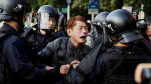 Riot police detain a protester near the Cabinet compound in Taipei, Taiwan, on Monday.