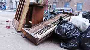 A mangled piano lies in a pile of garbage during cleanup efforts in New York City, following Hurricane Sandy in 2012.