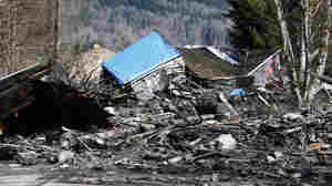 A destroyed house sits in muddy debris near Oso, Wash., on Sunday. A rain-soaked hillside let loose a wall of mud Saturday, inundating neighborhoods along the Stillaguamish River's North Fork.