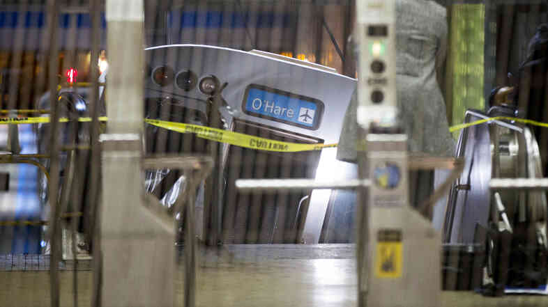 A derailed Chicago Transit Authority train car rests on an escalator at the O'Hare Airport station early Monday, in Chicago.