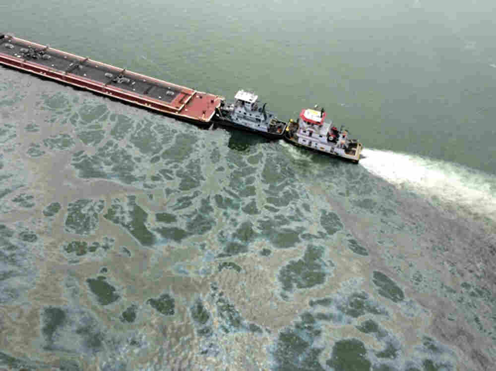 A barge loaded with marine fuel oil sits partially submerged in the Houston Ship Channel on Saturday.