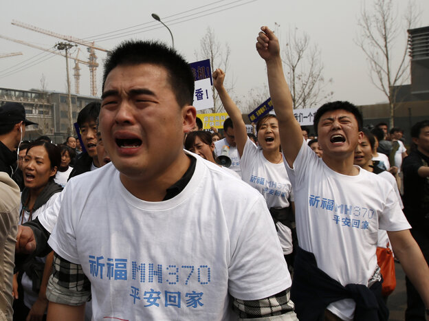 Family members of passengers aboard Malaysia Airlines Flight 370 tearfully shouted slogans du