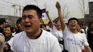 Family members of passengers aboard Malaysia Airlines Flight 370 tearfully shouted slogans during a protest Tuesday in front of the Malaysian Embassy in Beijing.