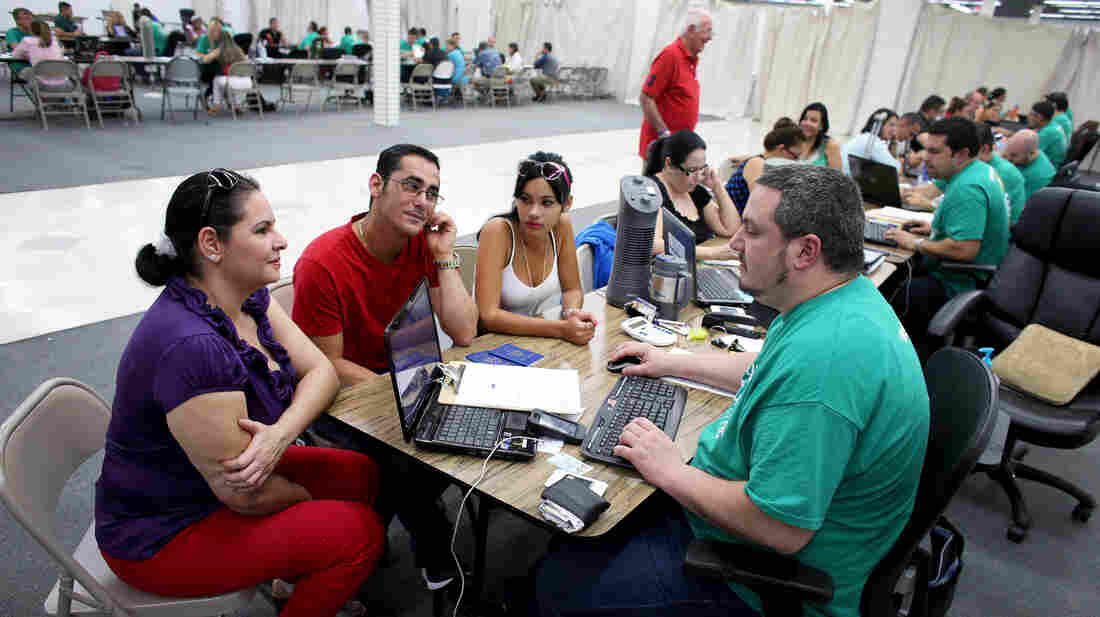 Yudelmy Cataneda, Javier Suarez and Claudia Suarez talk with insurance agent Yosmay Valdivian at a session to sign up for health insurance in a Miami mall March 20.