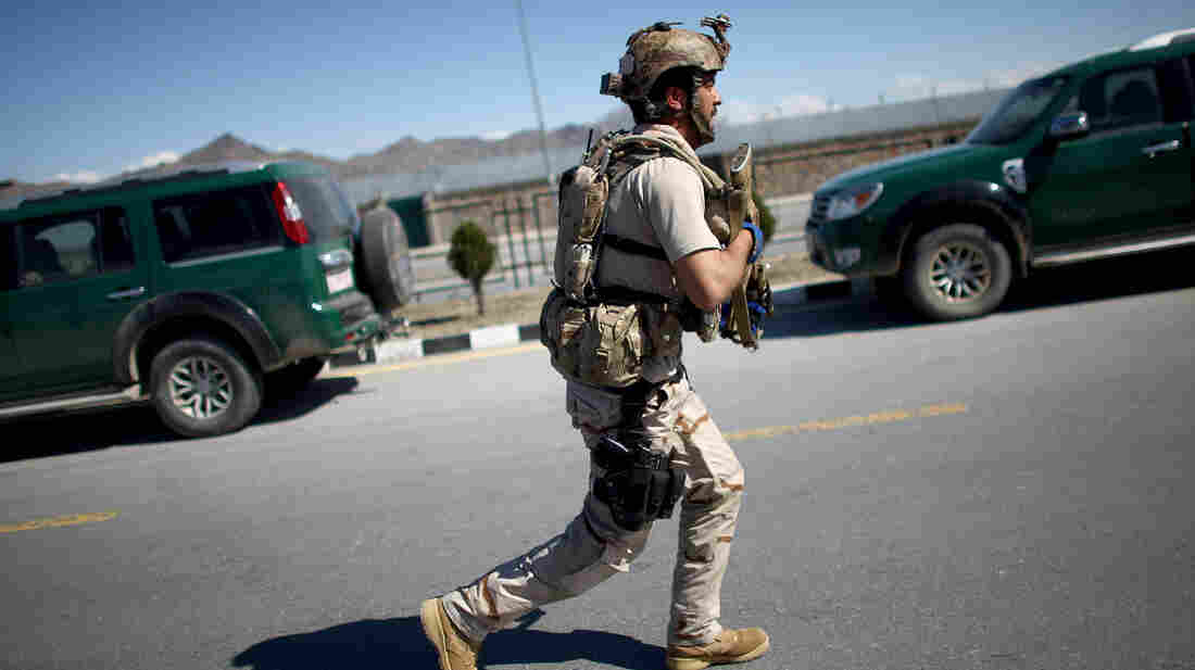 A soldier with the Afghan Special Forces approaches the main election office in Kabul following a Taliban attack. The Taliban have warned Afghans not to vote in the April 5 presidential poll.